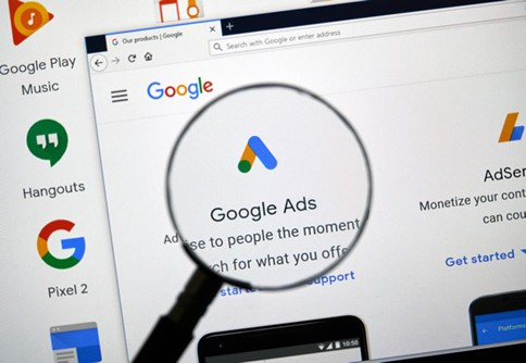 Magnifying glass highlighting the Google Ads logo and text